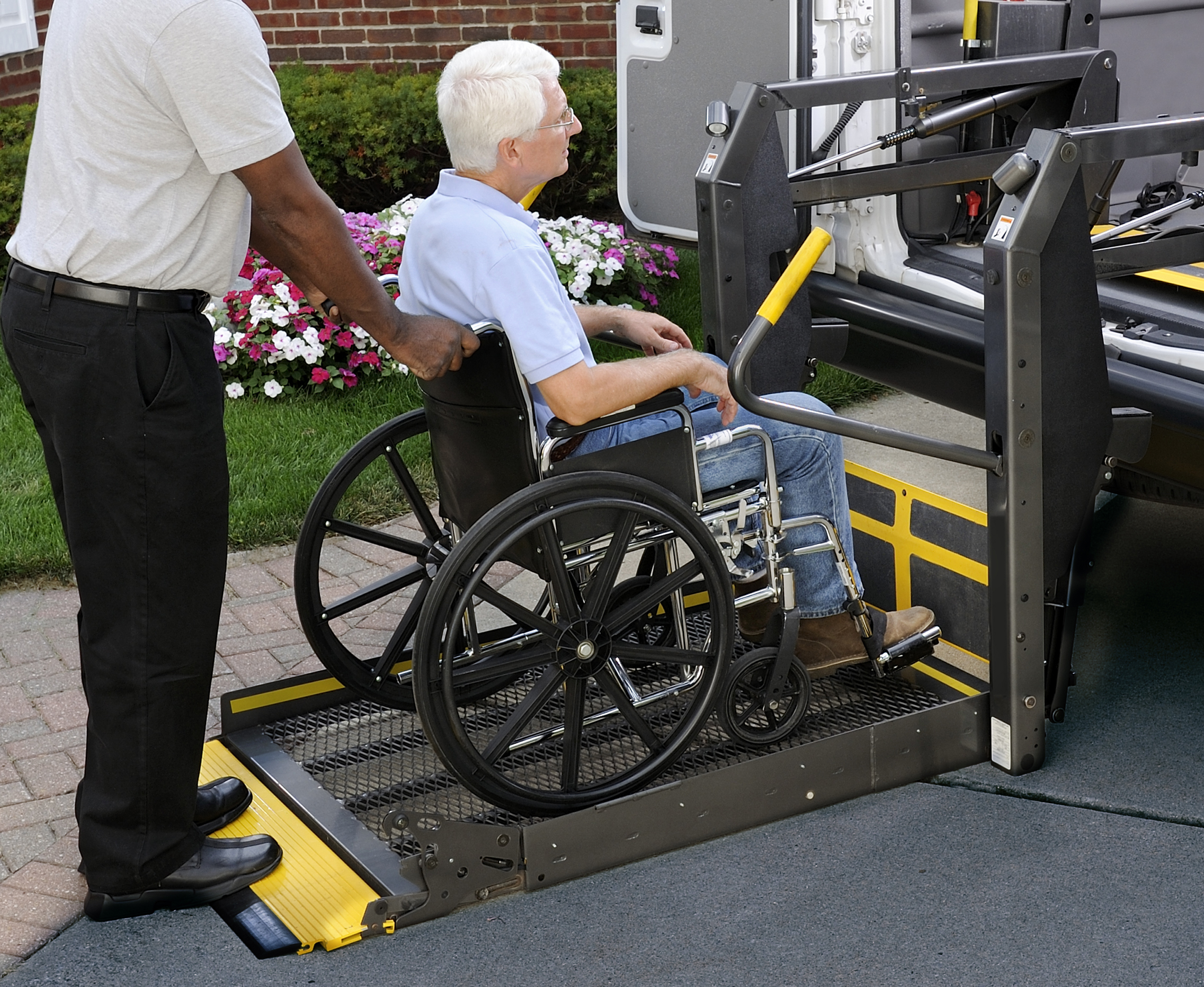 A non-emergency medical transportation representative is loading a wheel chair customer into a medical transportation vehicle.